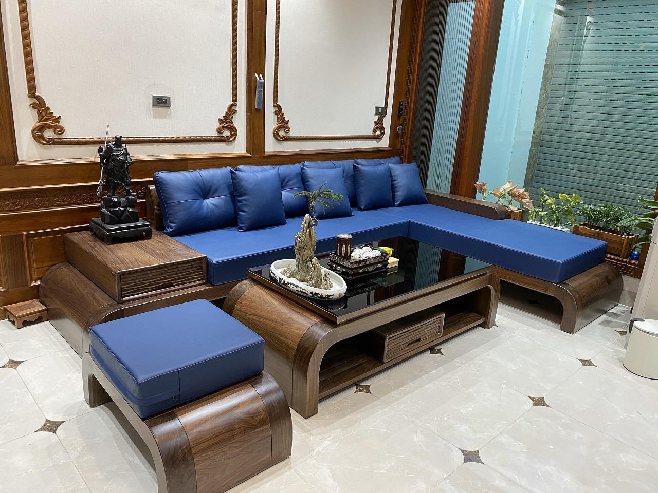 Bộ sofa nổi bật với bề mặt gỗ óc chó mịn màng và sắc xanh ấn tượng của chất liệu da cao cấp